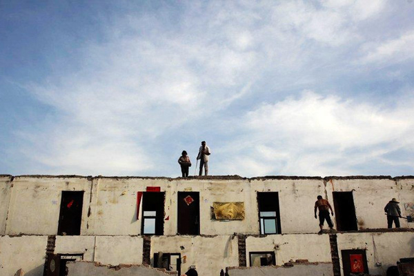 7月8日,拆迁中的北京唐家岭,工人们在工地上回收建筑材料。6月初,唐家岭集体土地上的违建进入自行拆迁期。 CFP  _财新每周图片(2010.7.3-7.9)