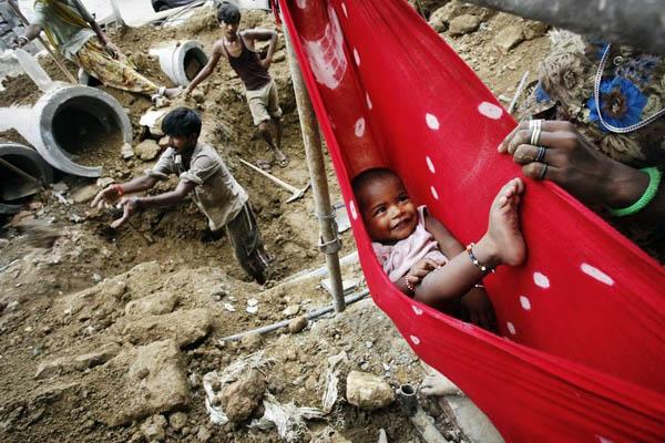 7月22日,在印度新德里康诺特商业区的一处建筑工地,一个小孩躺在吊床里玩,而他的家人正在工地上干活。英联邦运动会将于10月3日开幕,整个新德里到处是施工工地。 人民图片/Fotomore.cn  _财新每周图片(2010.7.17-7.23)