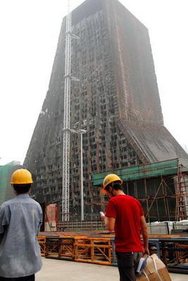 8月11日,央视新址被焚北配楼开始复建,工人们进入工地。 东方IC _央视被烧大楼正式启动拆卸复建工程