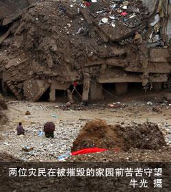 两位灾民在被摧毁的家园前苦苦守望