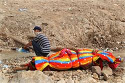 一位灾民蹲在废墟上等待搬运尸体