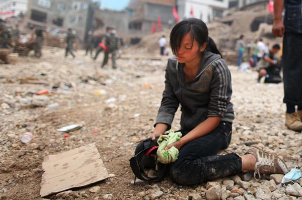 8月11日,一名在泥石流中失去亲人的灾民掩不住悲伤之情.