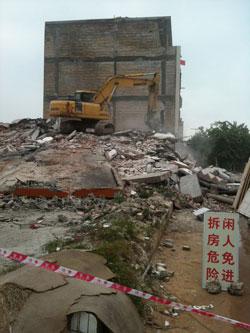 广西北海银滩镇,挖土机正在拆除一栋已将人清走的楼房