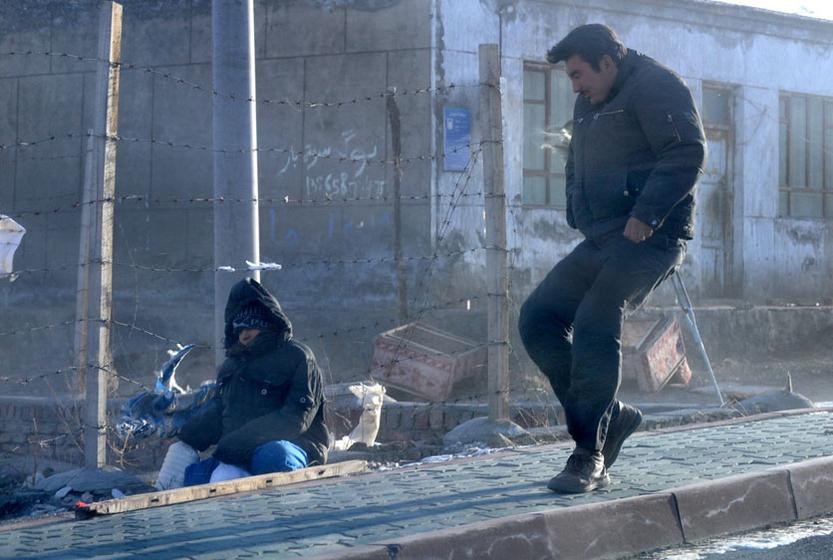 12月15日,乌鲁木齐市红雁池的哈萨克村,准备帮助孩子的男子也被大风刮