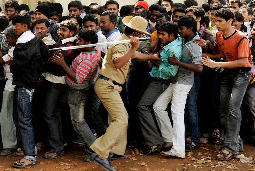 2011年2月24日,印度,班加罗尔,警察用棍子驱赶买票的人群站好队。世界杯板球比赛B组,印度和英格兰的比赛将在周日举行。 REUTERS _财新每周图片(2011.2.19-2.25)