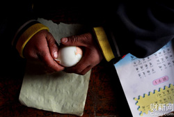 宁夏,固原市西吉县西滩乡。西滩中心小学一年级,刘定国,8岁,正在剥鸡蛋皮。