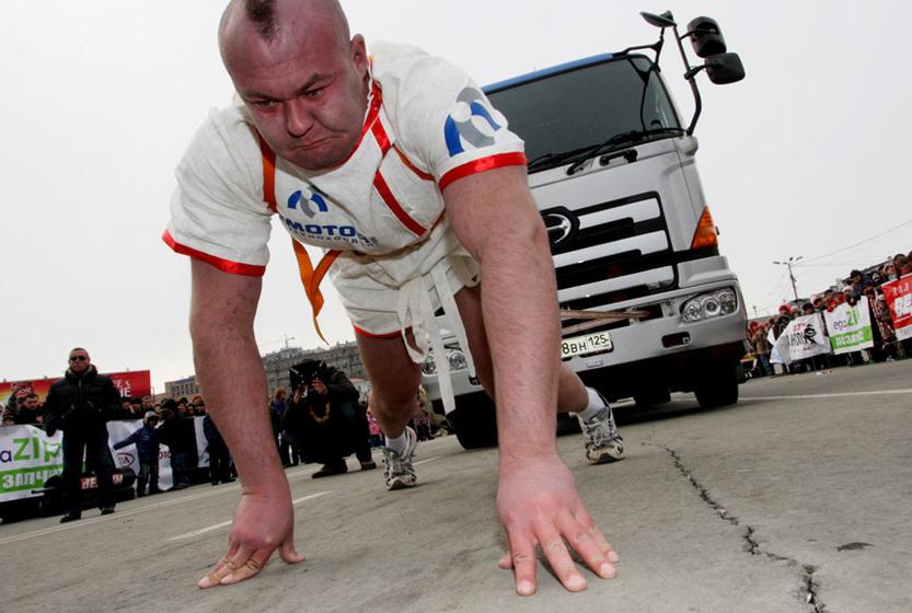 图为俄罗斯大力士在表演拉汽车