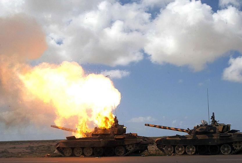 2011年3月20日,在利比亚城市班加西和艾季达比耶之间的一条公路上,一辆被联军袭击而燃烧的Qaddai军队的坦克。 CFP _多国军事行动 利比亚政府称64人在空袭中遇难