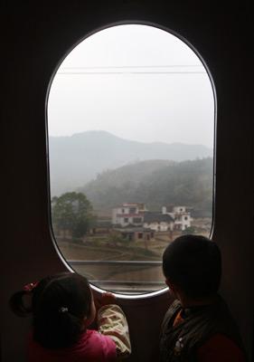 2009年12月26日上午9时,武广高速铁路客运专线列车从新广州北站火车站开出。             两个孩子趴在窗口看风景。陈帆/CFP