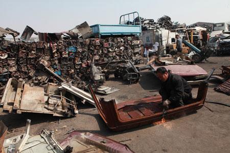 位于北京东郊的北京联合汽车解体厂内,工人正在切割报废的汽车。李漠 摄