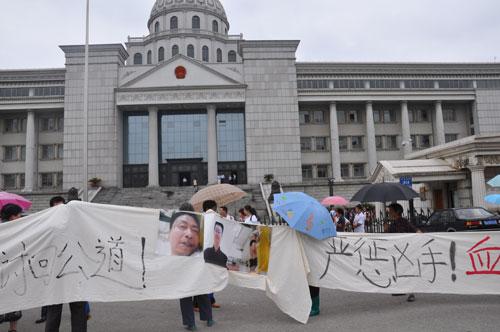 2009年7月1日,万建国被刑讯逼供致死案开庭,万建国家属在法院门口打出横幅。左志英 摄