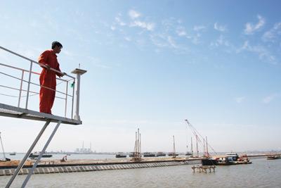 河北省黄骅港综合港区,工人们站在瞭望台上。今年上半年,河北钢铁集团在黄骅港的物流园将要动工,投资至少50亿元。郑荣玺/CFP