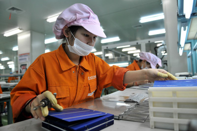 2011年3月24日,浙江某新能源股份有限公司制造车间,工人正在装配光伏电池片。随着多晶硅行业准入门槛的提升,不少大企业趁机扩产。郏策/CFP