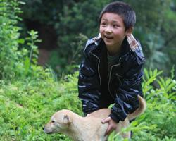 合兴村的魏太喜是幸运的,他的儿子魏海龙被强行带走后,又被要了回来。图为魏海龙正和他家的狗玩耍。