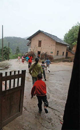 毛坪村在雨中玩耍的孩子。该村袁新权的女儿如果未被抱走,此时应是他们的玩