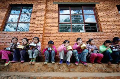 2010年3月31日,云南贫困山区一所小学里,孩子们蹲在简陋的校舍旁吃饭。中国90%的贫困人口集中于农村,目前的扶贫标准其实乃专门针对农村而言。沙浪/CFP
