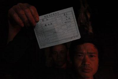 大石村的袁名友向记者展示他家的户口簿。户口簿上还有被抢走的女儿袁红的名字。