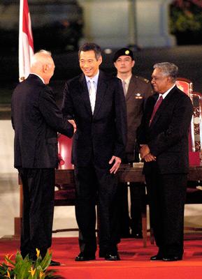 """2004年8月12日,新加坡新任总理李显龙(中)与父亲——新加坡""""国父""""李光耀(左)握手。1990年李光耀退职,继任者是吴作栋。李显龙同年成为副总理,直到2004年吴作栋辞职后他顺理成章地""""转正""""。Munshi Ahmed/Bloomberg/CFP"""