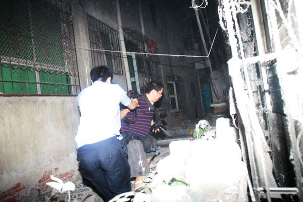 2011年5月19日,武汉,为为防止记者采访,硚口区政府和街道组织城管人员和社会青年封堵各路口,不让记者靠近现场,湖北一党报摄影记者在进入现场时,被城管死死抓住,拖出封锁口,该记者多处受伤,同行的当地另一家媒体记者拍摄下这一组画面。 周超/东方IC _武汉违建楼垮塌  政府组织城管围堵记者