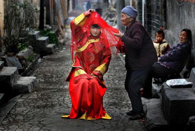 """安徽淮北一条老街上,一位老人帮助拍婚纱照的女孩整理盖头。""""六普""""公布的数据表明,老年人口比例要高于近年全国统计公报结果约1个百分点,老龄化程度事实上被低估。王文/CFP"""