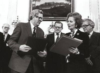 1985年11月15日, 菲茨杰拉德(左)在贝尔法斯特与英国首相撒切尔夫人签署完双边协议后交换文件。