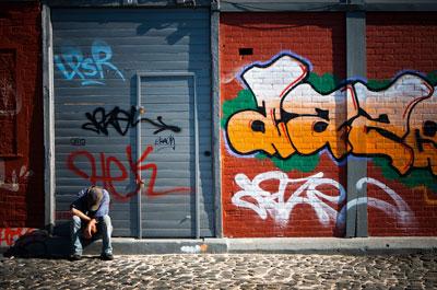 2011年6月1日,葡萄牙里斯本,一名男子坐在一家倒闭的商店门口。葡萄牙的公共债务占GDP的比例比希腊要低(约为95%),但是该国预算赤字十分庞大,严重负债的私人机构和经常账户赤字的规模都与希腊大致相当。Mario Proenca/Bloomberg/CFP