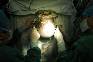 """2007年9月27日上午10时30分左右,武警福建总队医院脑外科立体定向中心手术室,一位精神病人头部被包上保护膜并固定,接受免费""""微创开颅""""手术。"""
