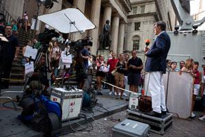一名电视记者站在纽约证券交易所外对着镜头做报道。