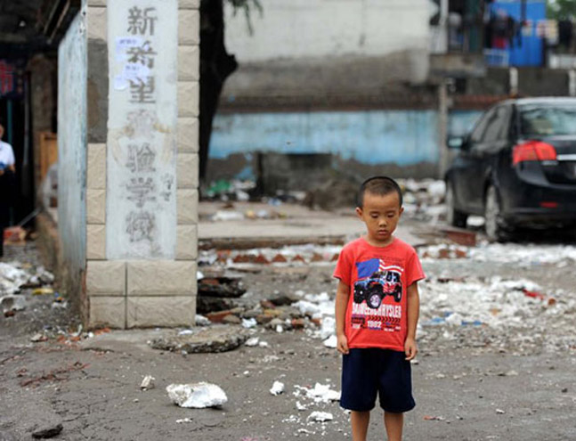 A small boy standing in the gate of one former school building now reduced to rubble. Photo by Wang Yixuan/CFP _Migrant School Demolished, Parents Furious