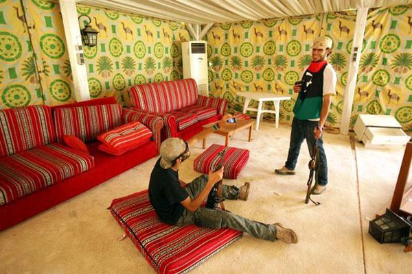 8月24日,利比亚反对派士兵在阿齐齐亚兵营内的卡扎菲住所拍摄纪念照片,卡扎菲曾在这里接待外国领导人。 PATRICK BAZ/东方IC  _反对派搜查卡扎菲及其子女豪宅