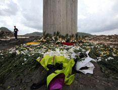 """2011年7月28日,""""7·23""""温州双屿动车追尾事故现场堆放着哀悼逝者的鲜花。40位遇难者的代价何其沉重。"""