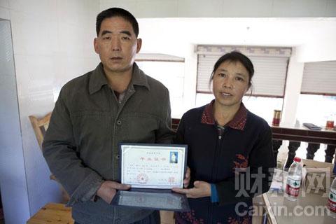 在成都富士康爆炸中去世的赖小东的父亲拿着他儿子的毕业证书