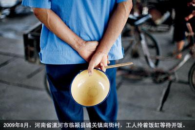 2009年8月,河南省漯河市临颍县城关镇南街村,工人拎着饭缸等待开饭。