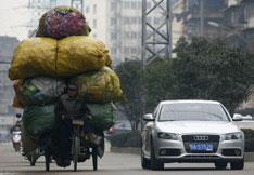 2010年2月23日,湖北武汉,一名回收废旧塑料瓶的小贩将回收到的瓶子运走。