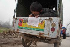 """近来全国各地接连发生校车事故,深层次原因是相关地区对教育投入不足,付出的代价是孩子们一次又一次伤亡。图为在家长自备的""""校车""""上写作业的孩子。"""