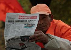 2010年11月20日,南京街头阅读报纸上税收报道的环卫工人。