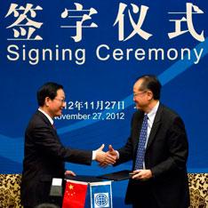 """2012年11月27日,北京,世行行长金墉(右)与中国财长谢旭人(左)举行""""世界银行-中国发展实践知识中心""""签字仪式。"""