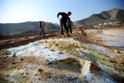 在甘肃白银市四龙镇民勤村东大沟附近,工人把掺了化学试剂的受污染土壤埋入改良工程淋洗池中。