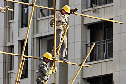 建筑工人在脚手架上盖楼