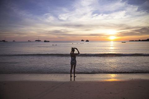 游客在用手机拍摄海边的夕阳