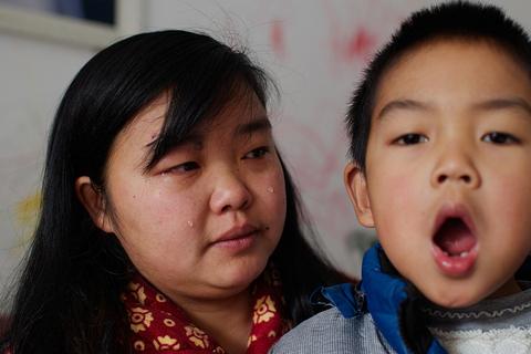 2015年1月10日,湖北武汉,钟鲜新和5岁的儿子汤睿。目前,汤睿患有严重的呼吸道疾病,每个学期有两个月在家和医院治病打针。她说,以前买了这个房子,每天早上空气清幽,听着鸟声起床,还经常有小鸟飞进家里。附近的垃圾焚烧厂开始运作后不久,小区和家里都是臭味,鸟儿再也没有了,一家三口陆续得病。现在,她举家准备搬回老家黄石市居住和养病。陈杰/视觉中国