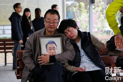 图:魏则西父母怀抱魏则西遗像