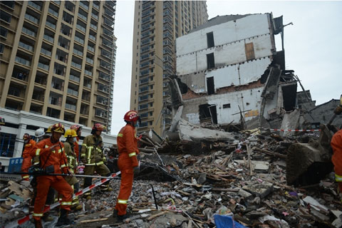 Rescue workers comb through the rubble at the site where four buildings collapsed in Wenzhou's Lucheng District on Monday killing 22 migrant workers. Photo: Visual China