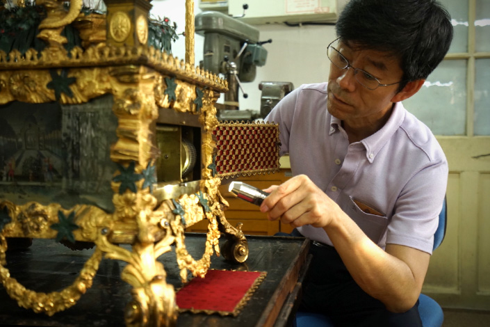 Wang Jin, a craftsman at the Forbidden City, restores a clock which used to belong to Emperor Qianlong. Photo: IC