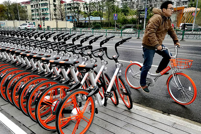 A man in Shanghai rides a Mobike Lite, a recent upgrade to the bicycle-sharing company's Classic Mobike model, such as those on the sidewalk, on Dec. 20. Photo: IC