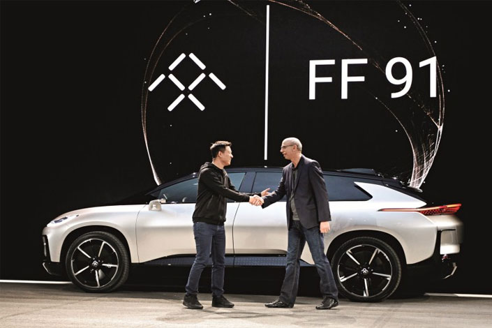 Jia Yueting (left), founder and CEO of LeEco, shakes hands with Nick Sampson, Faraday Future's senior vice president of product R&D and engineering, in front of a Faraday Future FF91 electric car at its unveiling at the CES 2017 electronics trade show in Las Vegas, Nevada, on Jan. 3. Photo: CFP