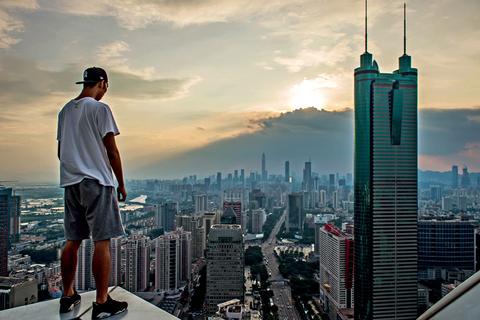 在深圳罗湖,青年站在高楼楼顶,摩登大楼与低矮公房错落有致.