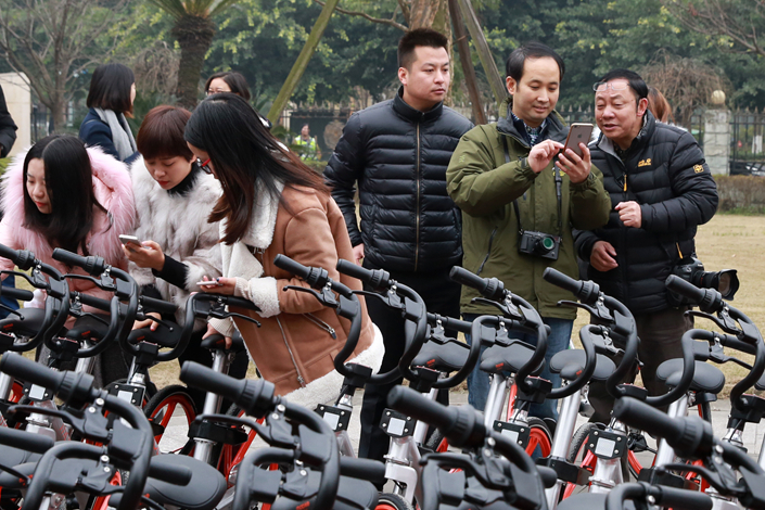 """Bicyclists check out Mobike offerings for rent in Pengzhou, Sichuan province, on Jan. 24.  Beijing Mobike Technology Co. Ltd. has announced a """"strategic partnership"""" with China Merchants Bank in which the bank will handle the bicycle deposits Mobike gets from its users. Photo: IC"""