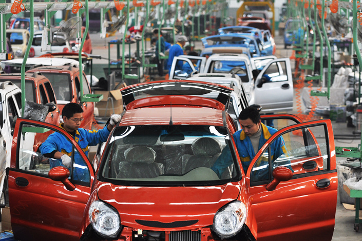 Chinese workers assemble electric cars on the assembly line in Binzhou, Shandong province, on Oct. 27, 2013. Sales of electric cars in China grew by 30% in February, rebounding from a plunge in sales in January that followed the central government's cancellation of the list of vehicles eligible for subsidies. A new list was published at the end of that month. Photo: IC