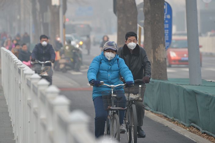 Bicyclists ride along Beijing's smog-shrouded Wangfujing Street on Dec. 31. The Ministry of Environmental Protection said the concentrations of PM2.5 and PM10 particulate matter in the Beijing-Tianjin-Hebei area rose sharply year-on-year in the first three months of 2017.  Photo:IC